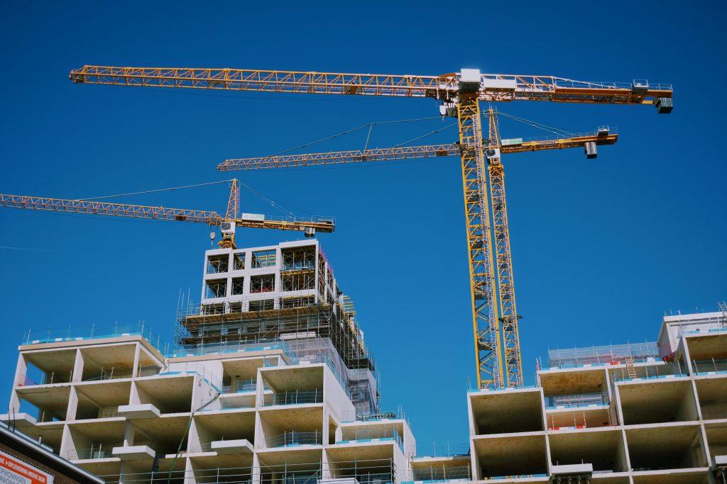 Tall yellow crane assembling condominium on pre-construction property